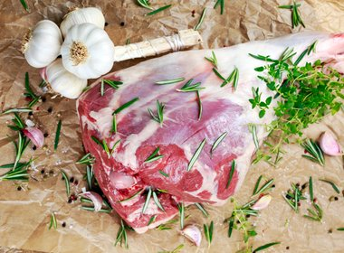 Raw lamb leg on crumpled paper background with her.jpg