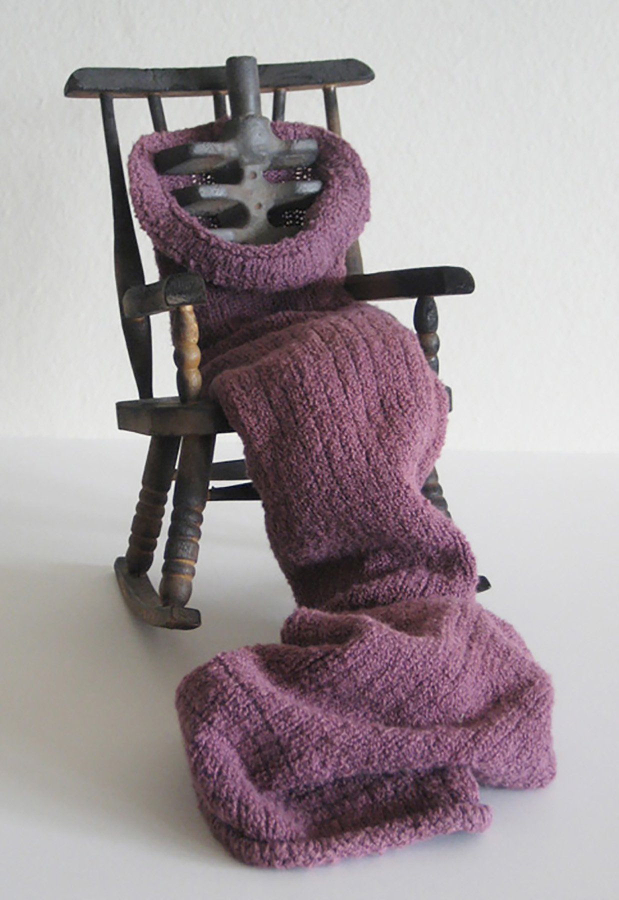 "Portrait of My Mother Dying, 8.5"" x 6"" x 11.5"", Found wood rocking chair, leg warmer, and found iron casting, 2004"