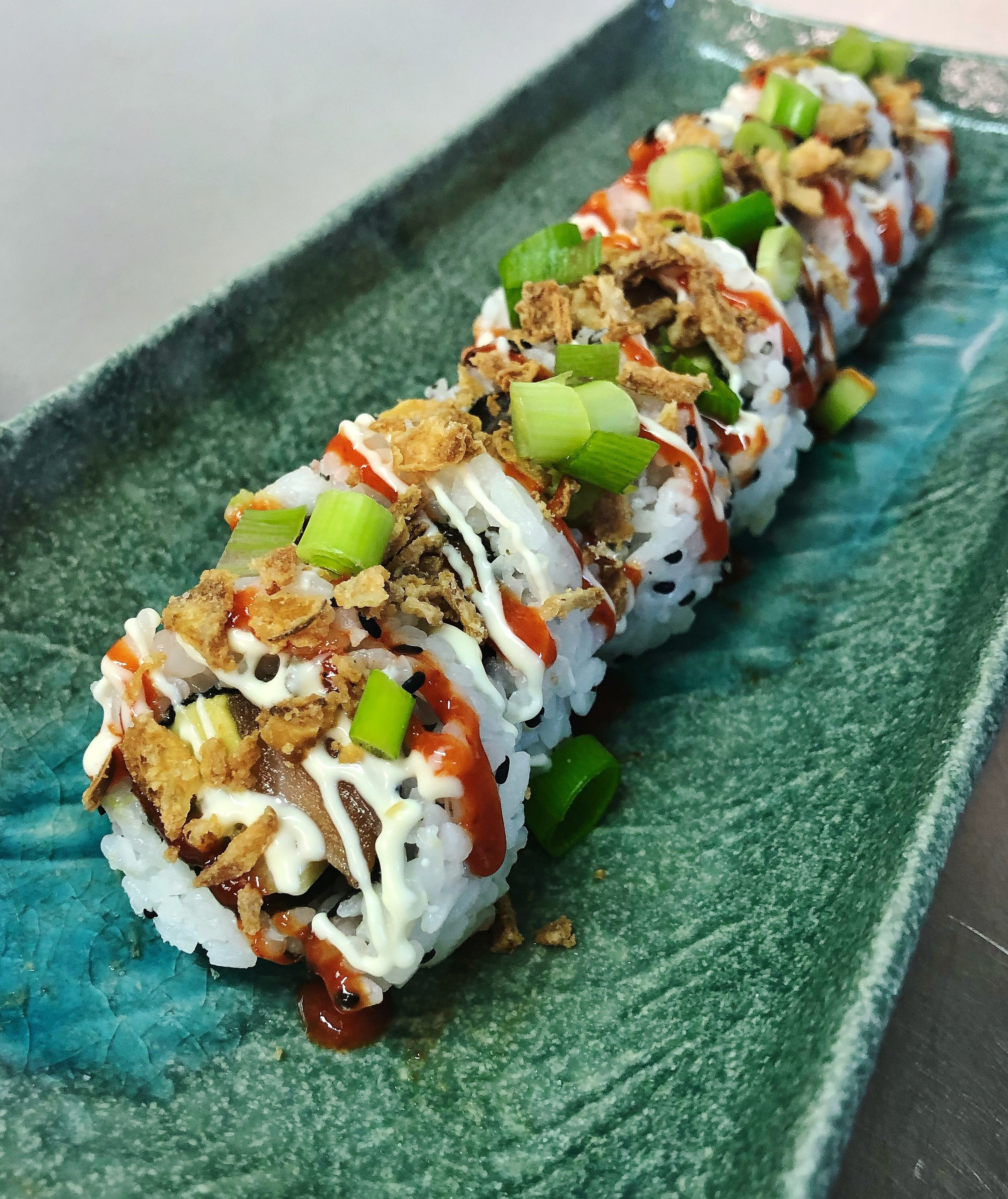 Spicy Salmon Crunch Roll - £7 *contains gluten *  filled with salmon, avocado, cucmber and topped with sriracha, Japanese mayo and crunchy fried onions