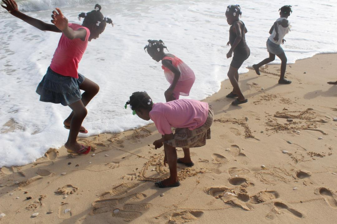 Haitian children dodging the warm waves of the Caribbean.