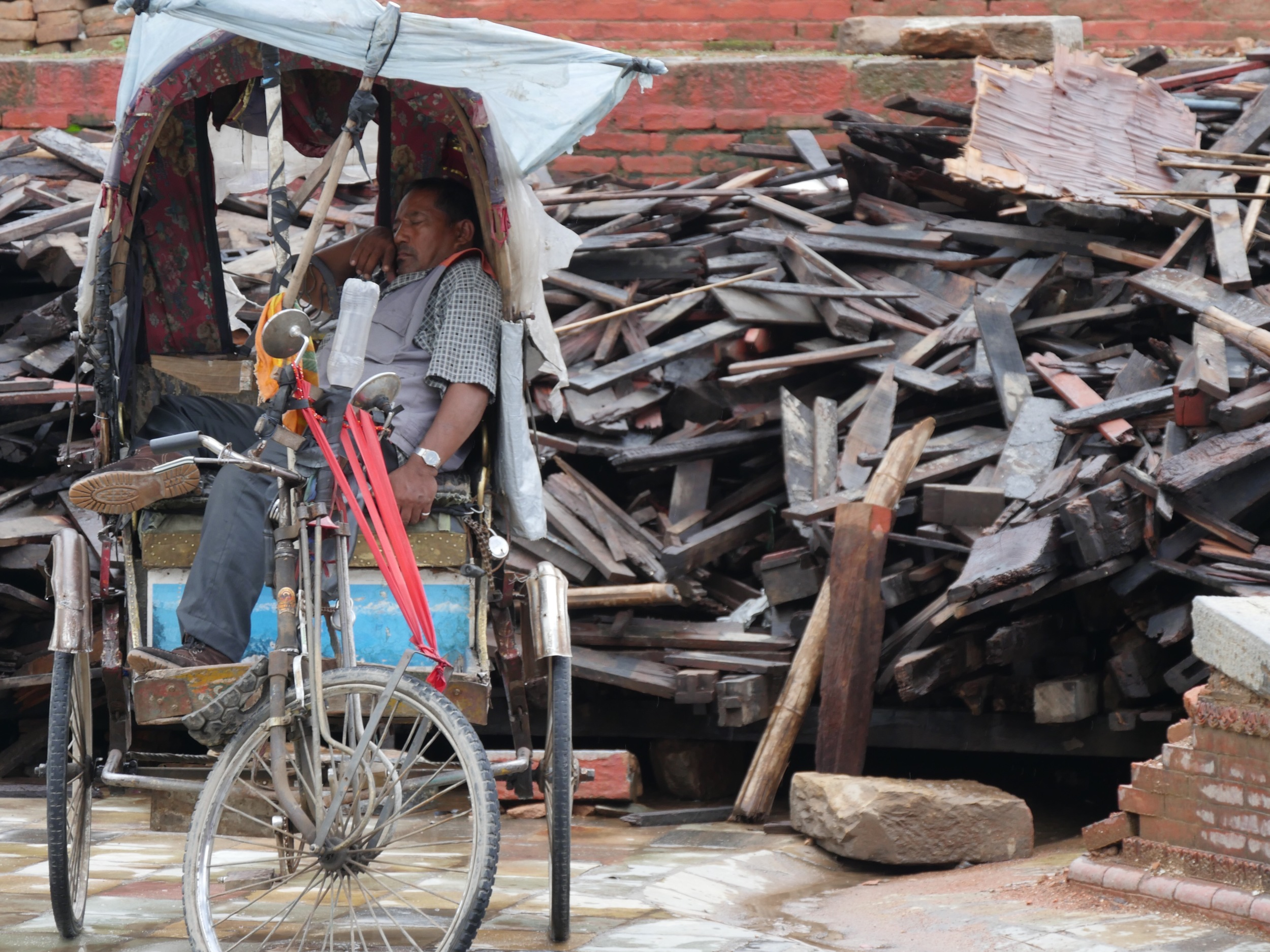 A rickshaw driver waits for customers against the backdrop of earthquake salvage.