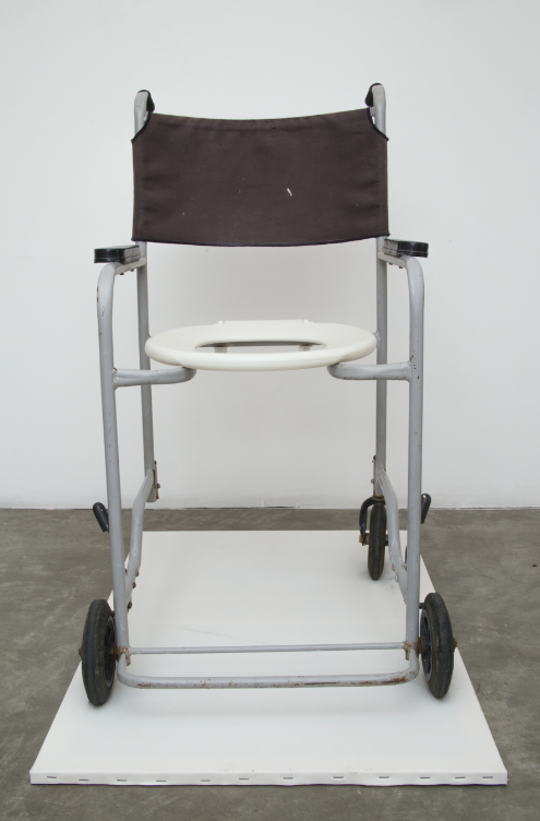 CONTEMPORARY ART STILL LIKES TO QUESTION THE CANVAS   18/1 2016, 90 x 60 x 95 cm, handicap toilet chair with one missing wheel on a white canvas