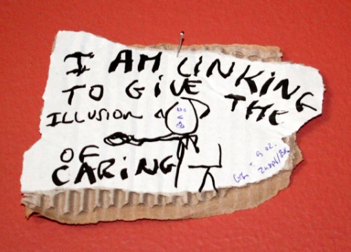 I am linking to give the illusion of caring, black marker and blue pen text and drawing on carton, 15 x 10 cm