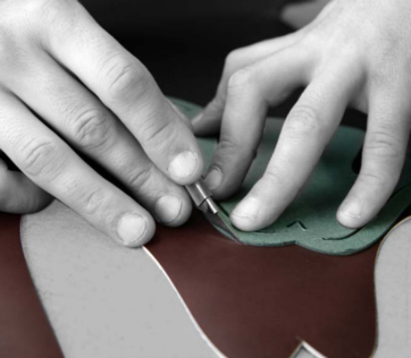 """STEP 2 - CUTTING THE VAMP - The vamp, or upper, is the top part of a shoe, consisting in a moulded piece that is sewn to the sole. Cutting (or """"clicking"""") the vamp is a task that only a true expert who is deeply familiar with leather can perform with the necessary care, using only the finest part of the hide. During the operation, the cutter must follow the """"grain"""", i.e., the texture of the leather, to make the shoes as supple and durable as possible. Selecting the best sections of leather also entails a greater degree of waste, and thus higher production costs."""