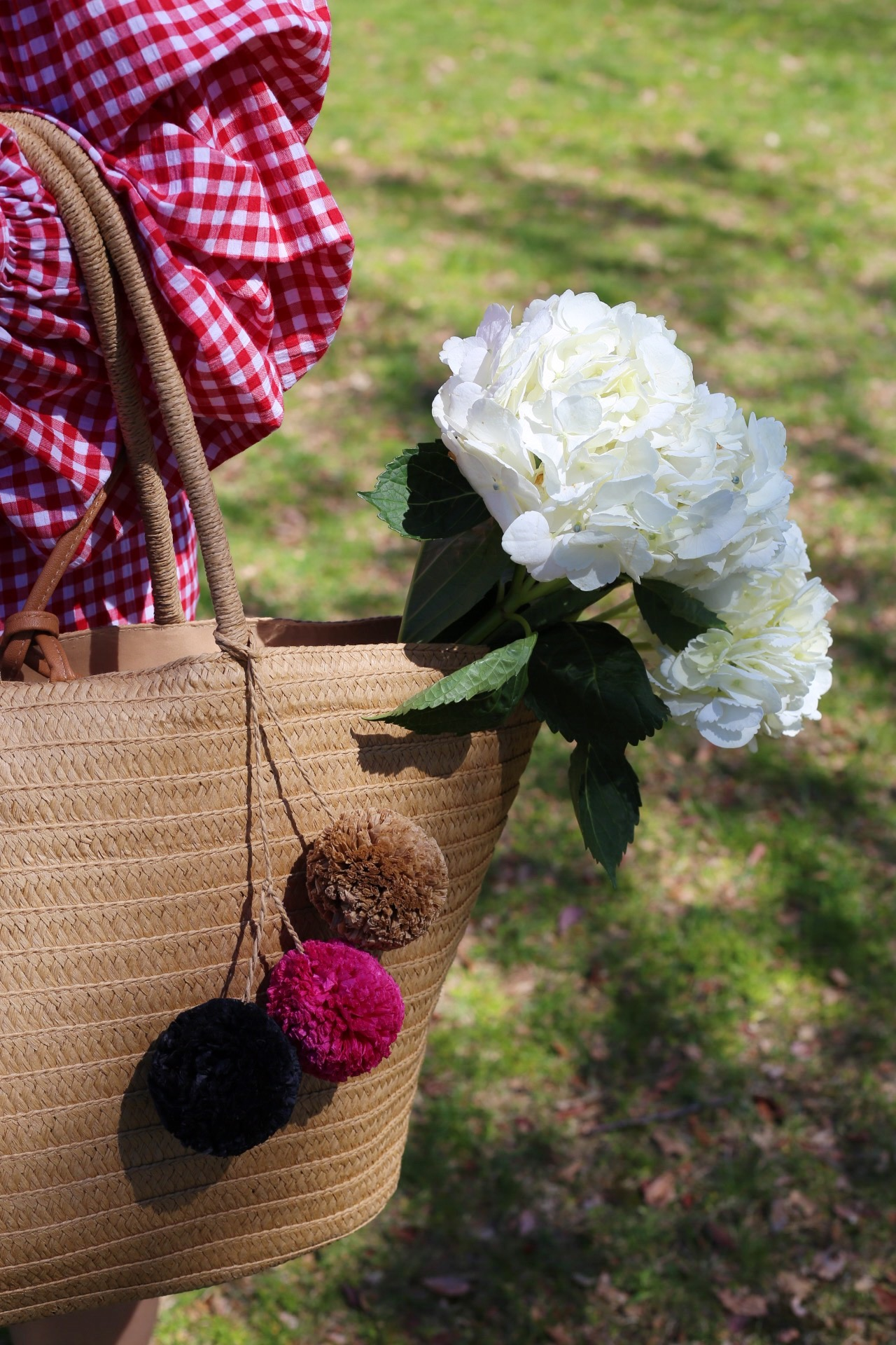 straw bag with pom poms