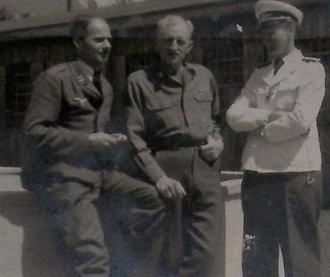"Scharff is on the left, an American POW is in the middle, and a Luftwaffe officer on the right.     ""YOU SHALL TELL US WHAT WE WISH TO KNOW, OR HERR OFFICER AND I SHALL HAVE TO... uh... make a note of that and send you back with some coffee to share with the others."""