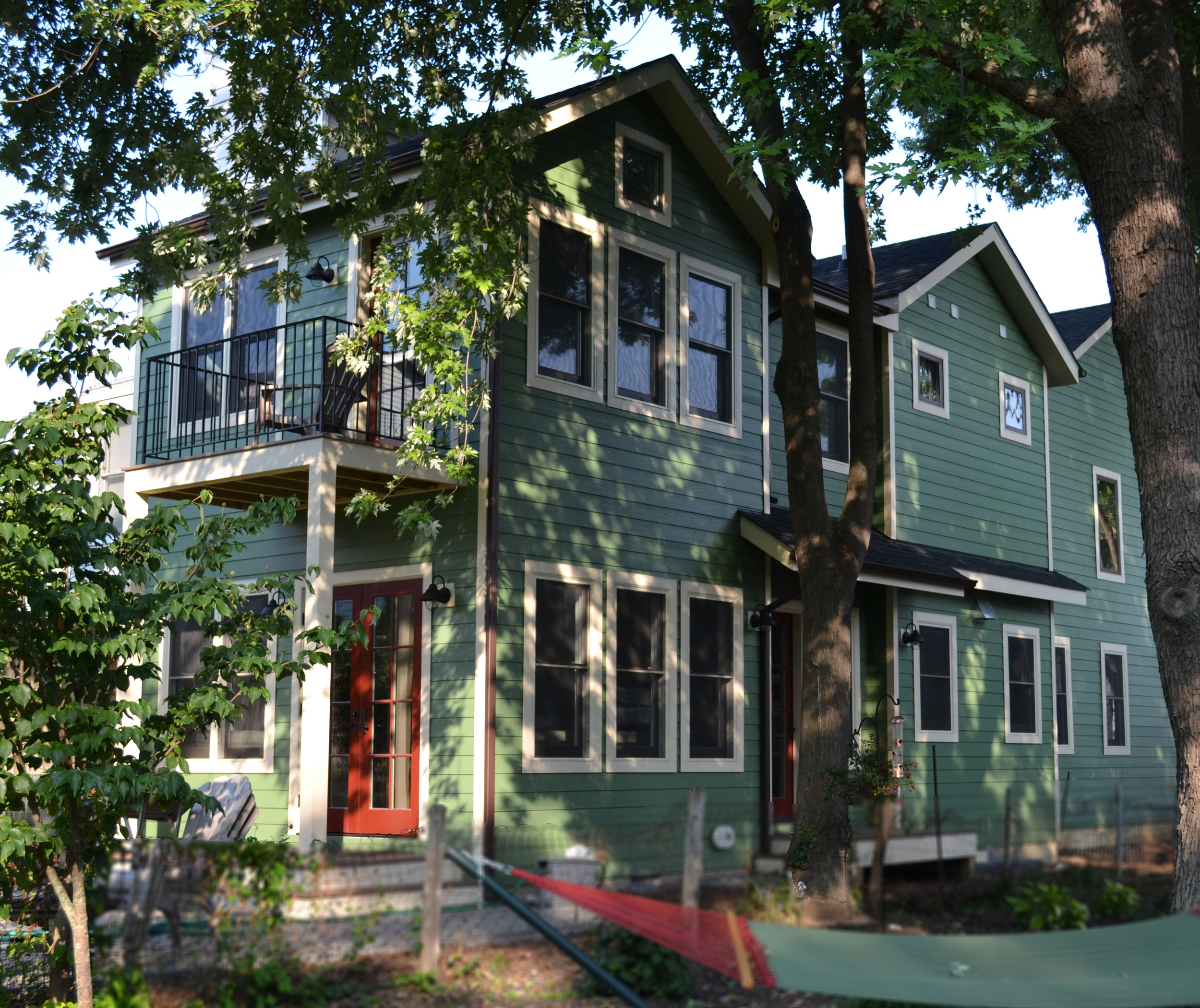 After - additions and renovations to the duplex adding interior program and bringing back to scale with its neighbor.