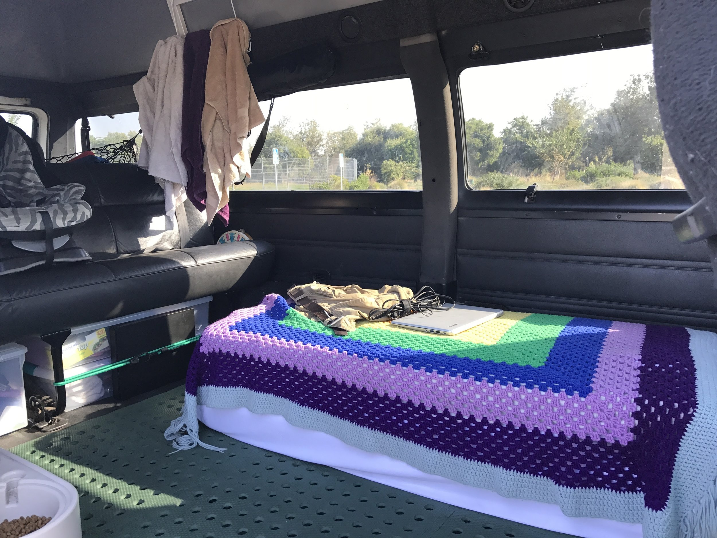 An average living room look into the van. The bed is folded up being used as a couch.