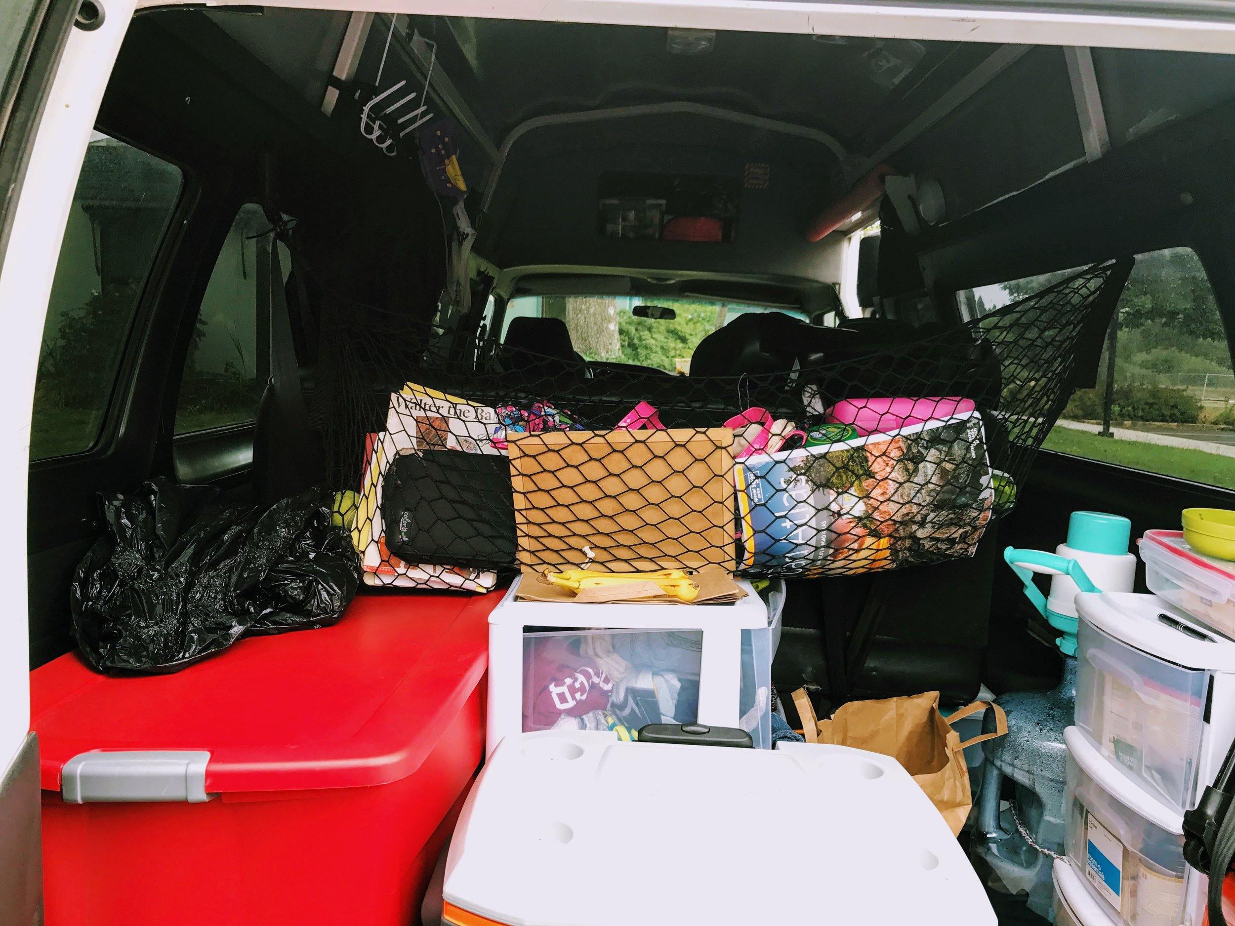 """The back of the van: The Coleman """"Fridge"""" the misc net, the food pantry, clothing behind the fridge, the dirty laundry bag, and the infamous red tote. This part of the van gets messy so quickly."""
