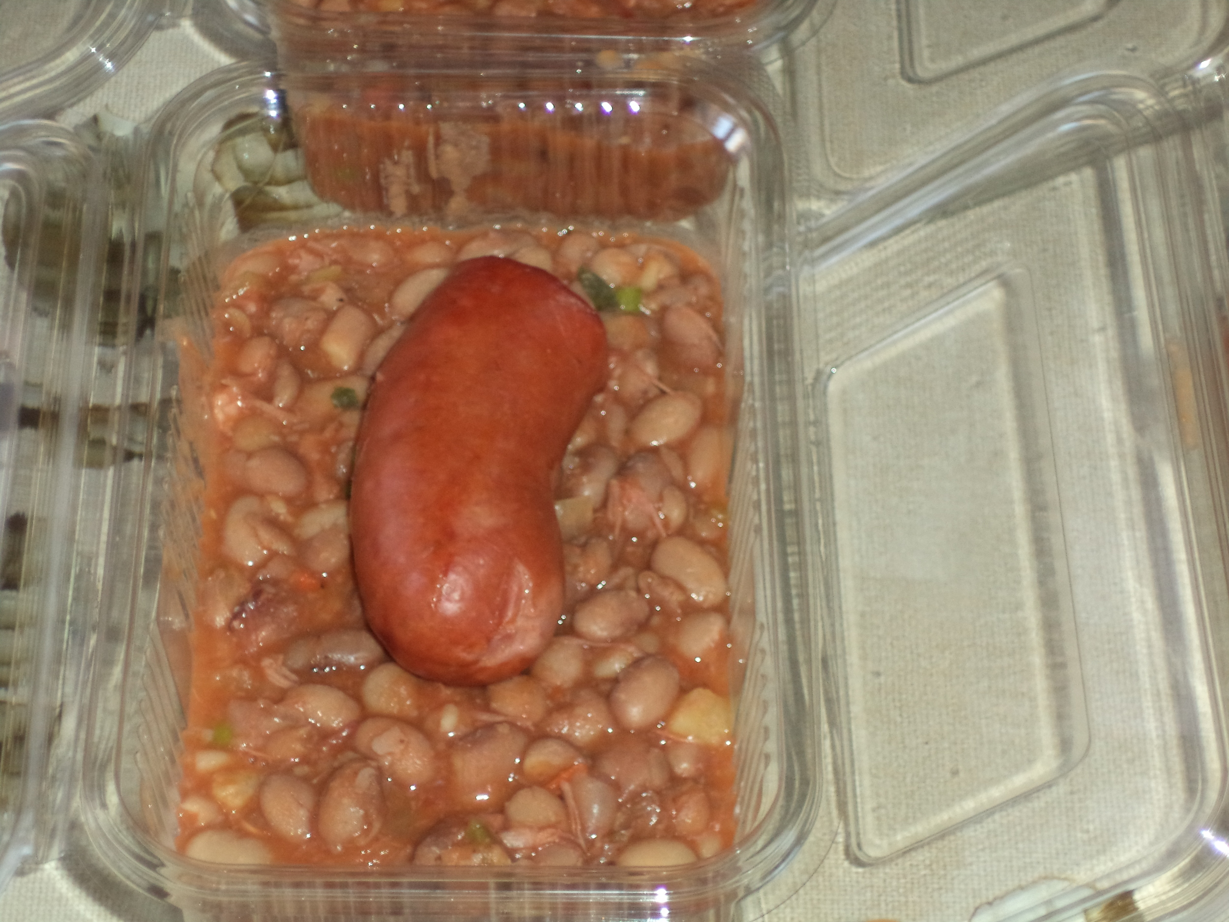 Sausage and homemade beans served with bread and fruit.