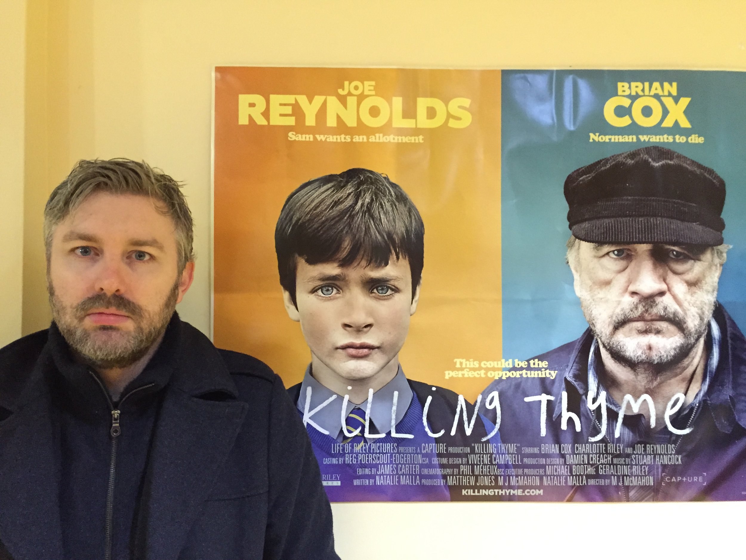 M J McMahon in front of Killing Thyme poster