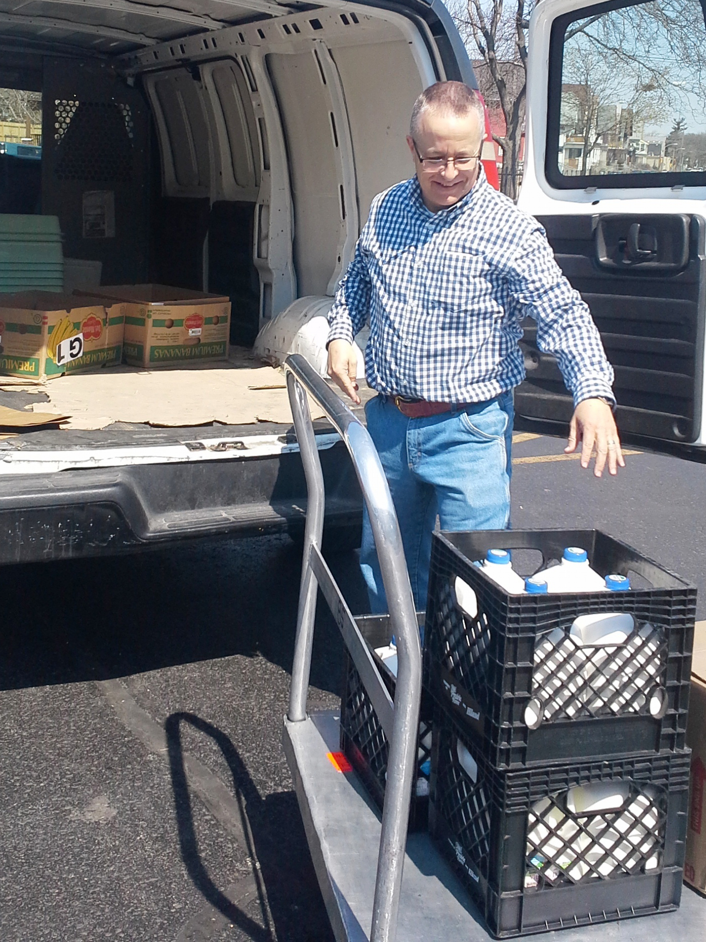 Bob loads fresh milk into the van with a smile on his face.