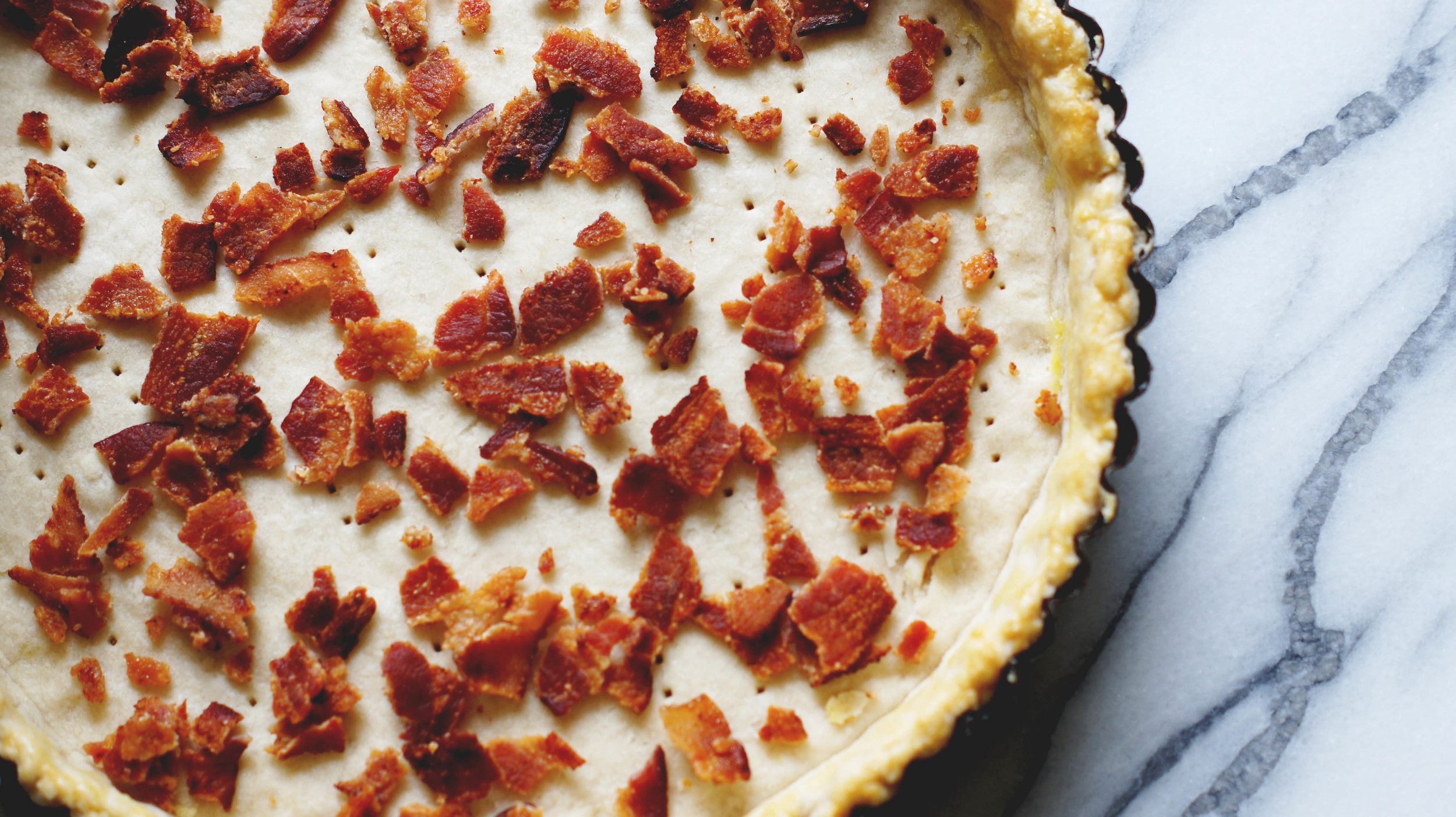 The blind-baked and cooled crust with bacon sprinkled across the bottom.
