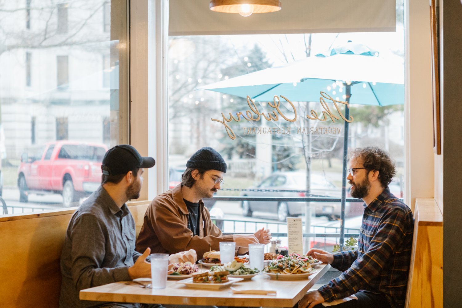 A photo of a table of people enjoying vegetarian and vegan food at The Owlery Restaurant in downtown Bloomington, Indiana.