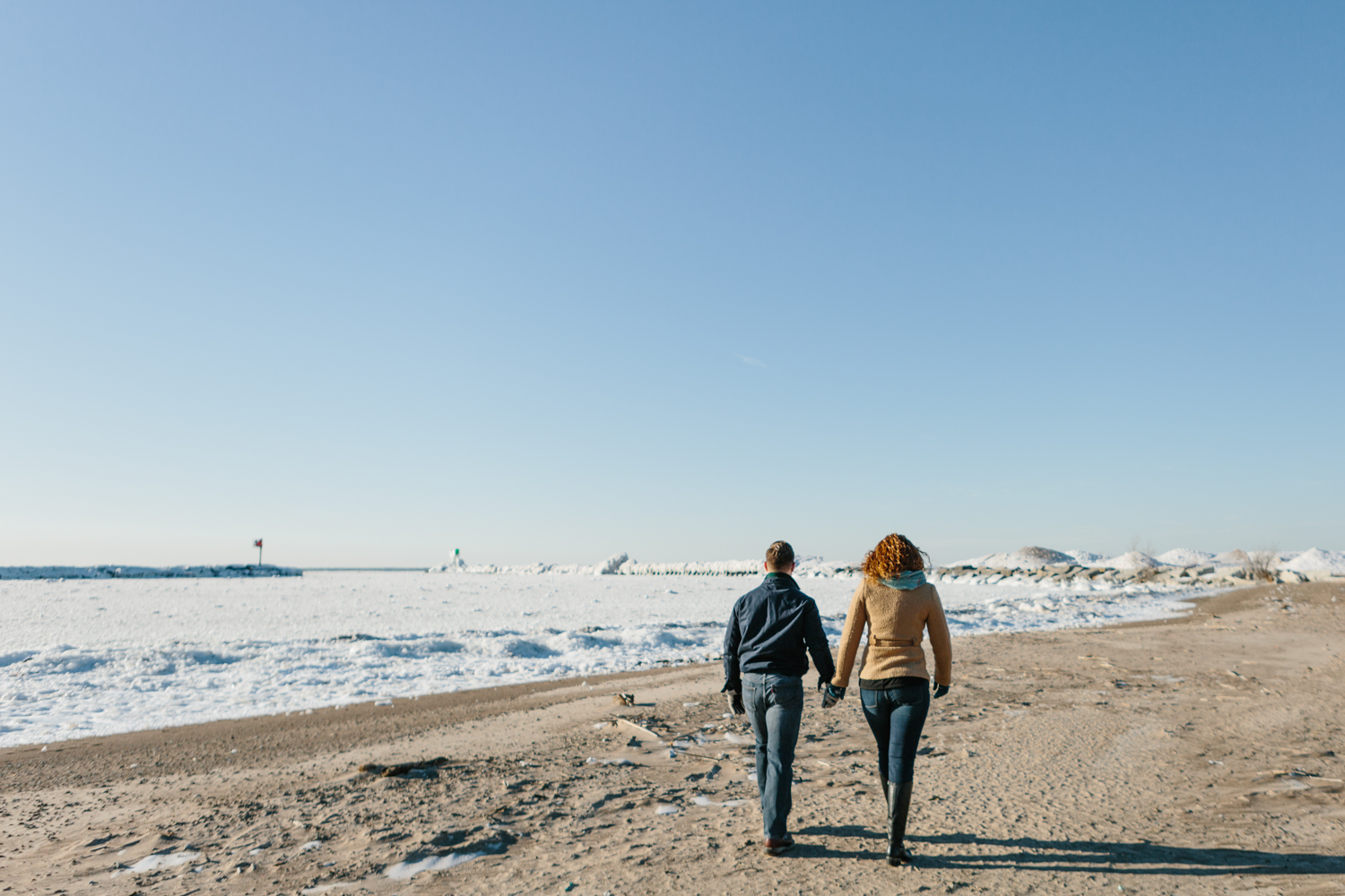 A couple walks along Lake Michigan during their Midwest engagement session.
