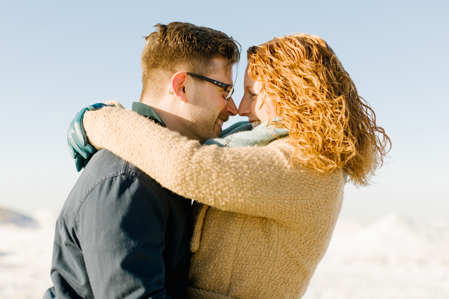 A photograph of a couple holding each other during their Midwest engagement session in New Buffalo, Michigan.