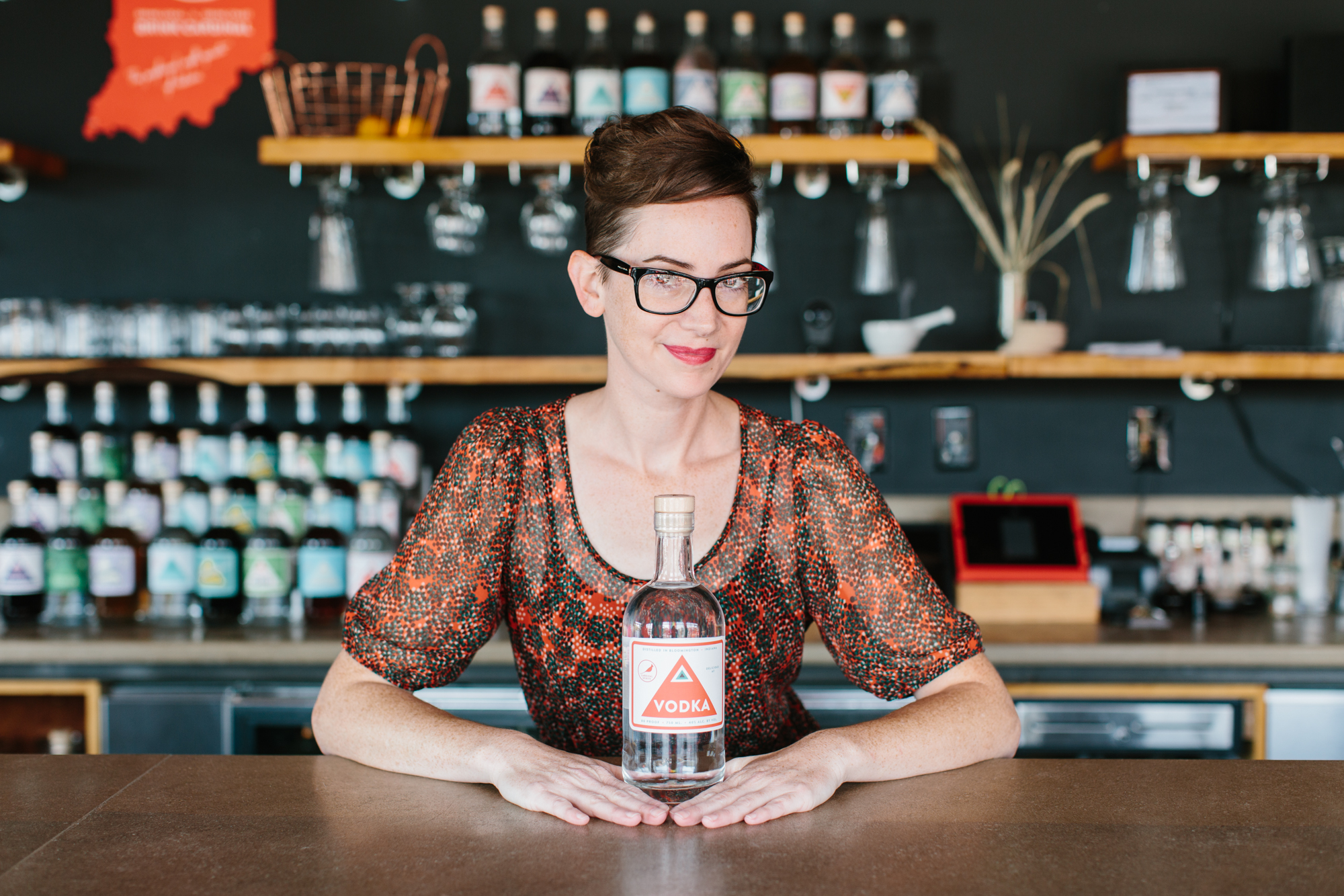 An editorial portrait of a woman at Cardinal Spirits in Bloomington, Indiana.