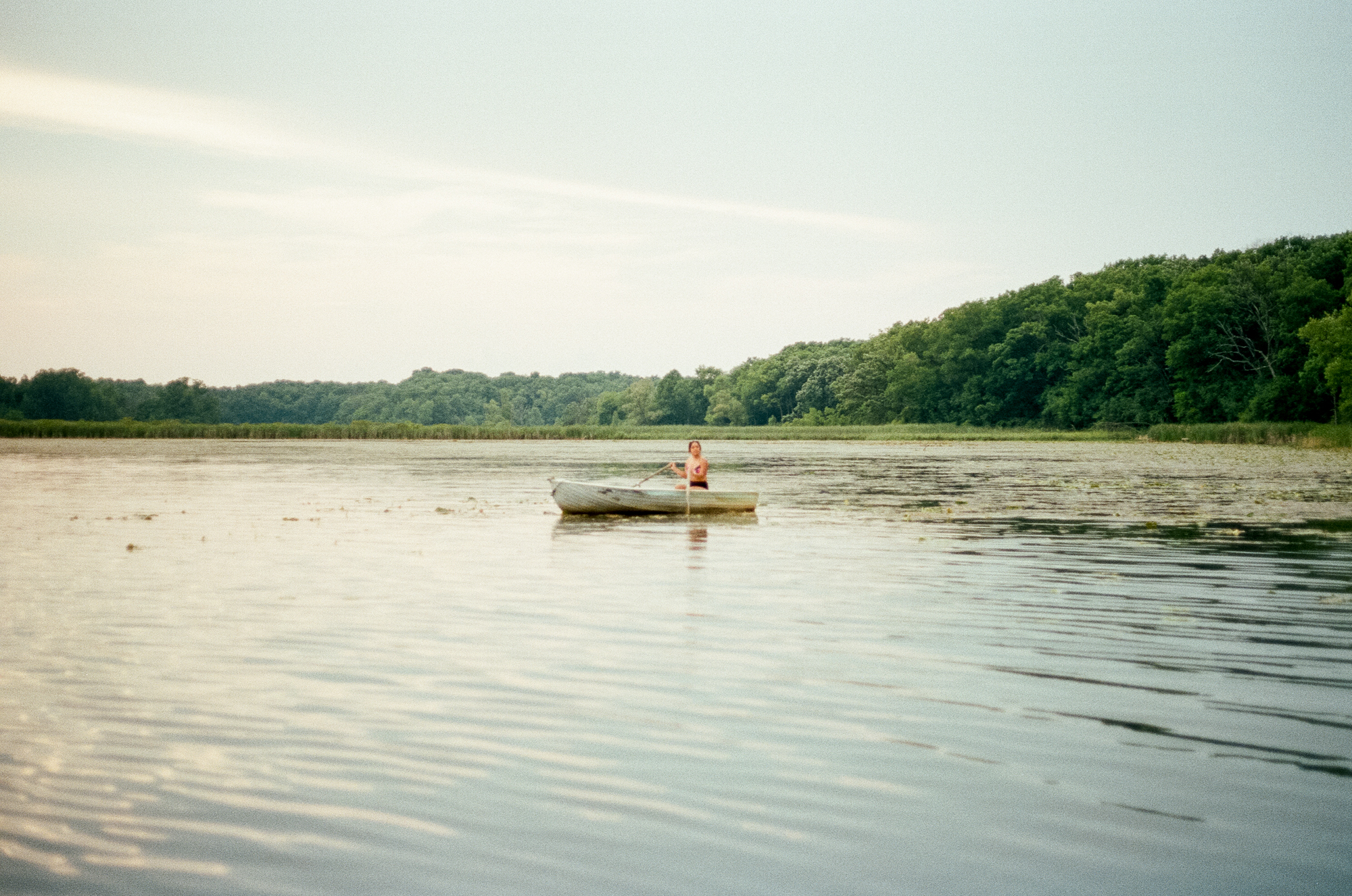 A photo of a woman kayaking at  Camp Wandawega  in Elkhorn, Wisconsin during Let's Camp 2018 photographed for  Driftless magazine  and hosted by  The Glossary  and  Feminest .