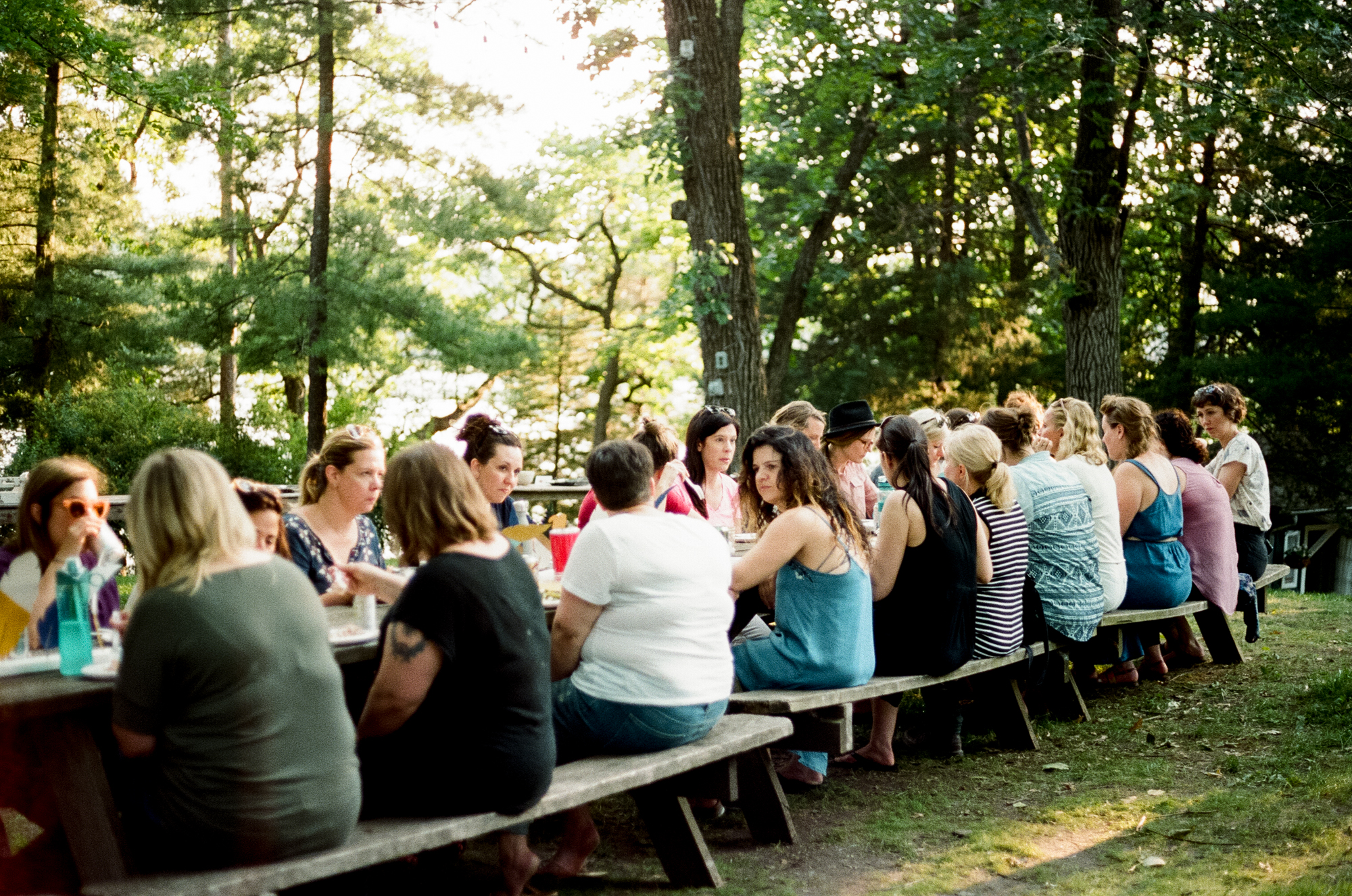 A film photo of women eating dinner at  Camp Wandawega  in Elkhorn, Wisconsin during Let's Camp 2018 photographed for  Driftless magazine  and hosted by  The Glossary  and  Feminest .