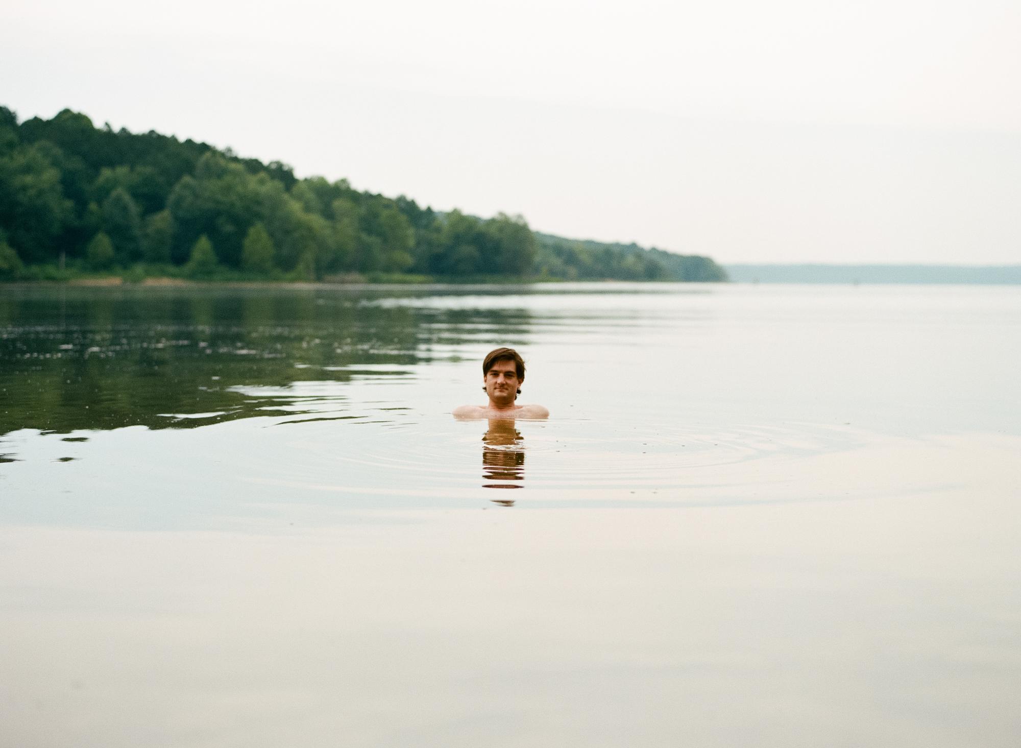 A portrait of designer Aaron Lowell Denton in Lake Monroe in Bloomington, Indiana.
