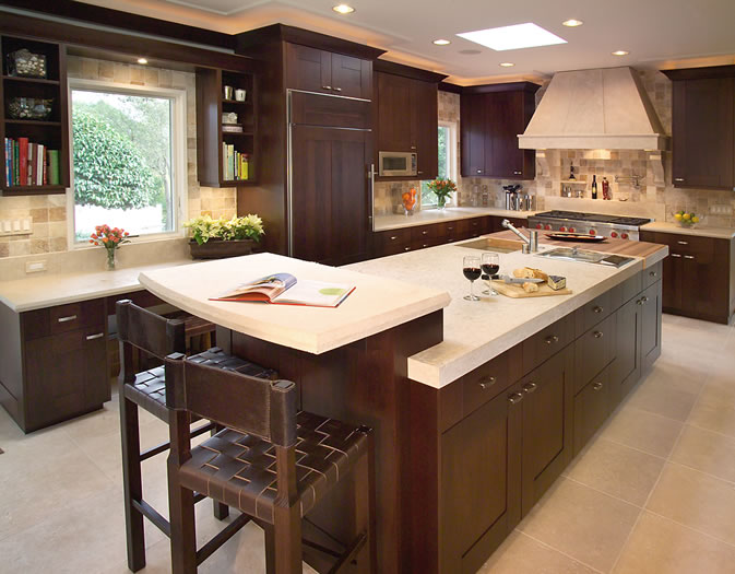 The dark cherry cabinetry gives strong contrast to the limestone counters.