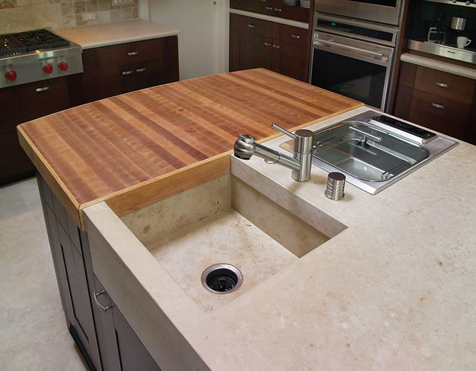 The end grain cherry butcher block abuts the custom stone sink and steamer.
