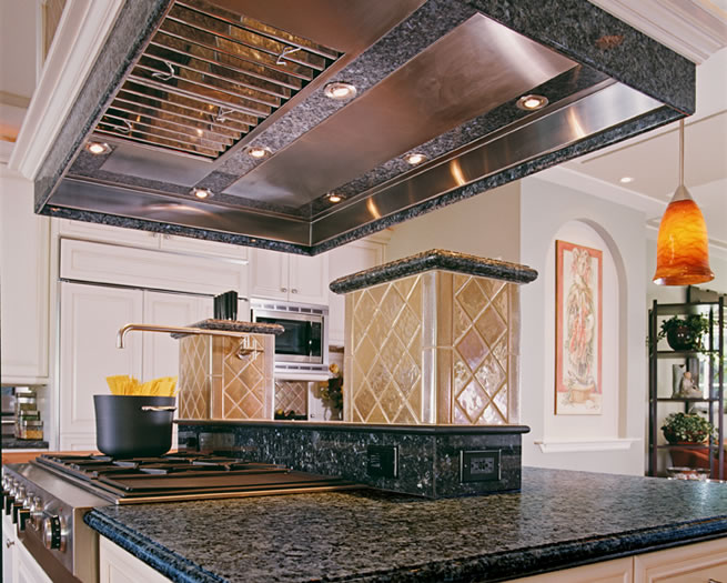 This custom range hood has a stainless steel liner with granite inlay and integrated lighting.