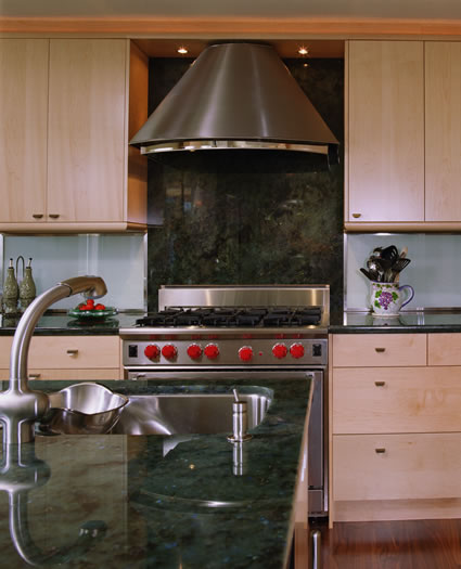The custom stainless steel hood mounted on the slab granite splash is this kitchens focal point