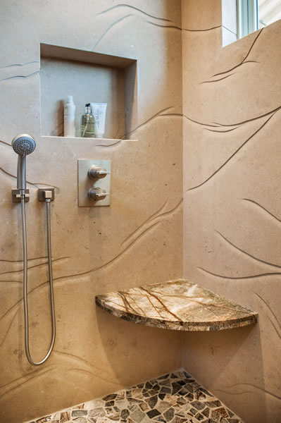 The hand carved limestone slab walls provides a flowing sense of movement to this shower.
