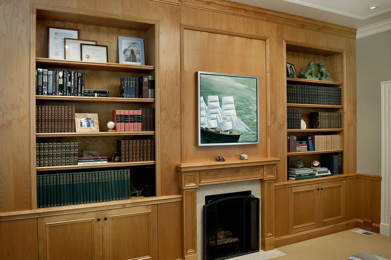 This stained alder office wall incorporates the existing fireplace.