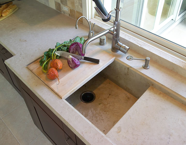 Limestone sink with movable cutting board.