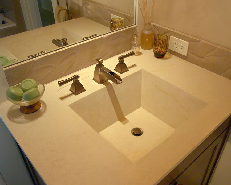 Limestone sink with relief at the faucets and carved limestone splash.