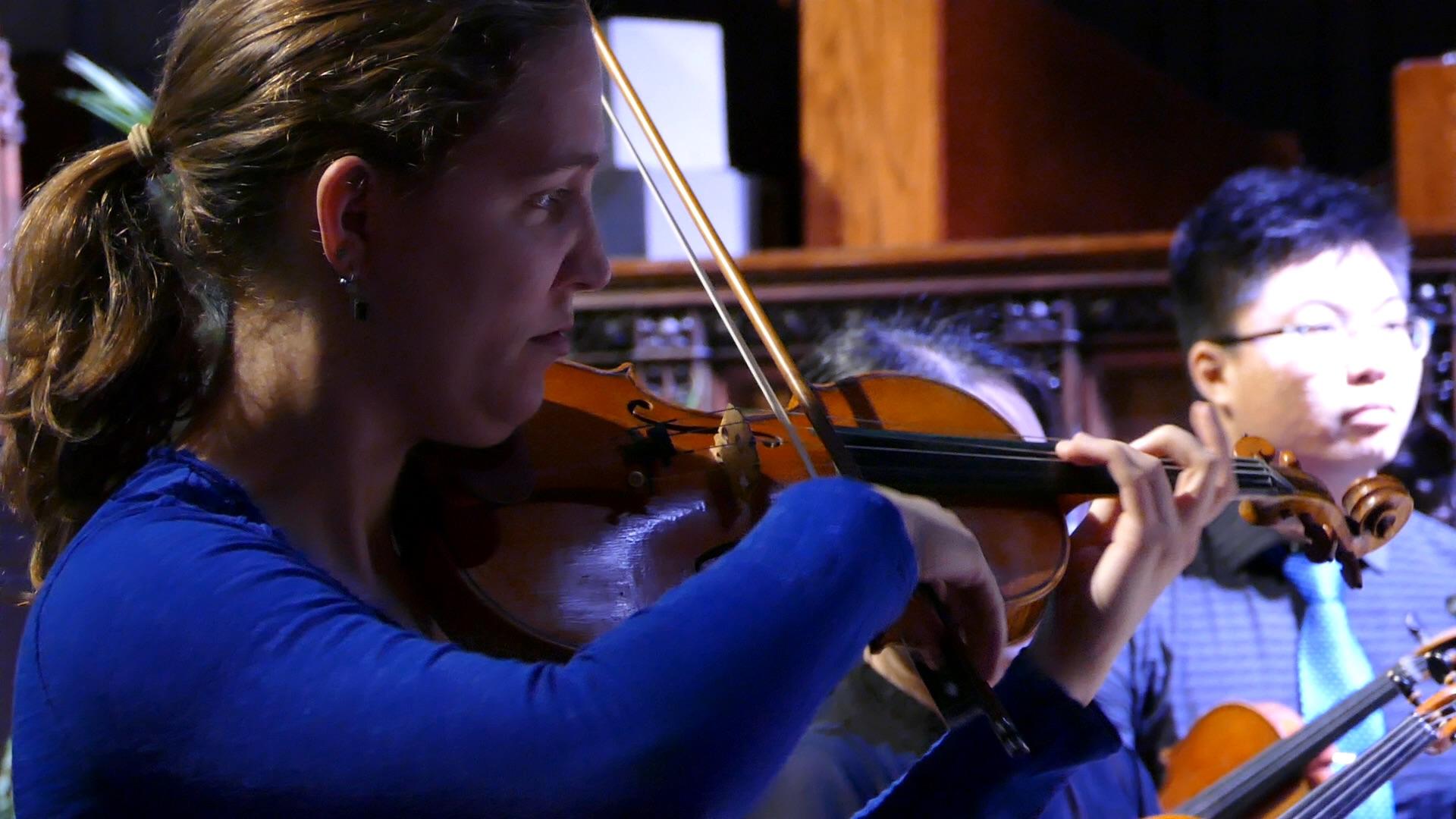 Former Associate Concertmaster Kristin Bakkegard leads the orchestra