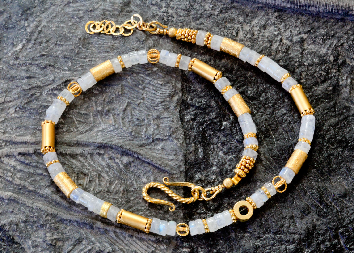 Slender glow of icy moonstones designed with 24K vermeil accents enfolds the neck comfortably like a light hug. Necklace is closed with 18K brushed vermeil hook clasp. Adjustable length 16 inches. (Can be lengthened with chain.)