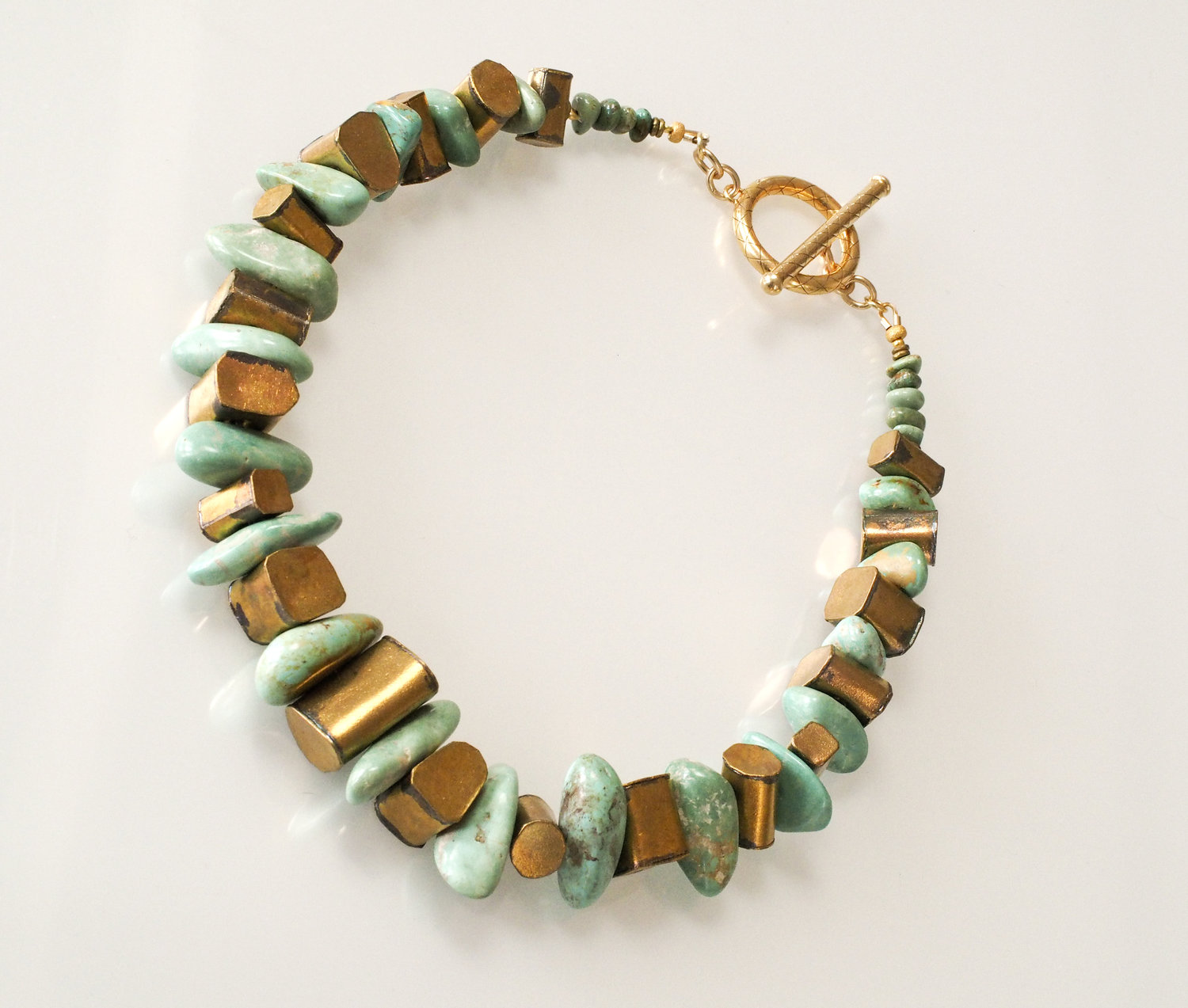 Brass geometric shapes alternating with Turkish turquoise chunks, closed with stunning 24K vermeil toggle clasp. Length 18 inches.  Materials: Turkish turquoise, 24K vermeil, brass  ID #1718103