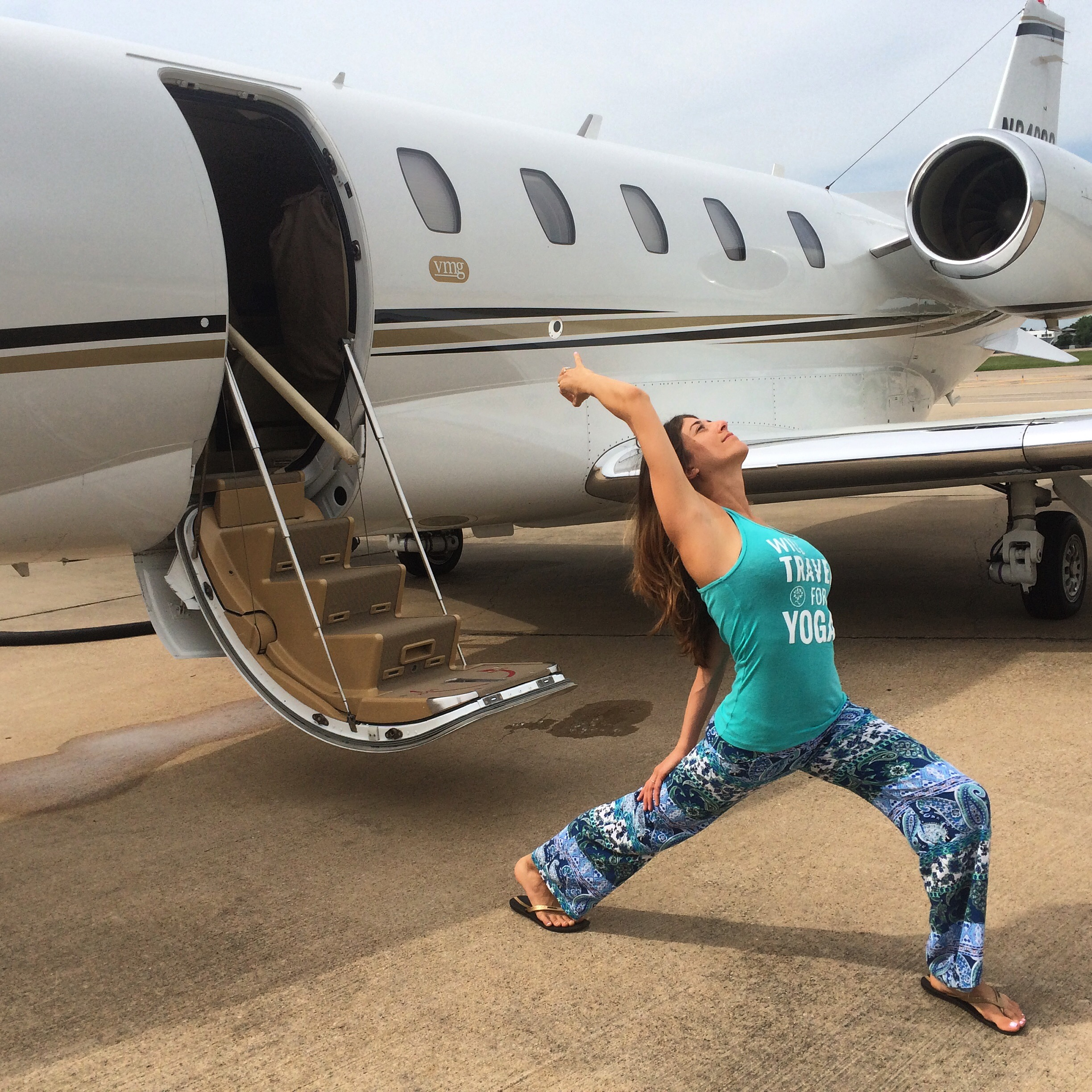 """Outside the jet, doing my #Stopdropandyoga, reppin' my @yogatraveltree """"Will Travel For Yoga"""" tank - a staple on my journeys!"""