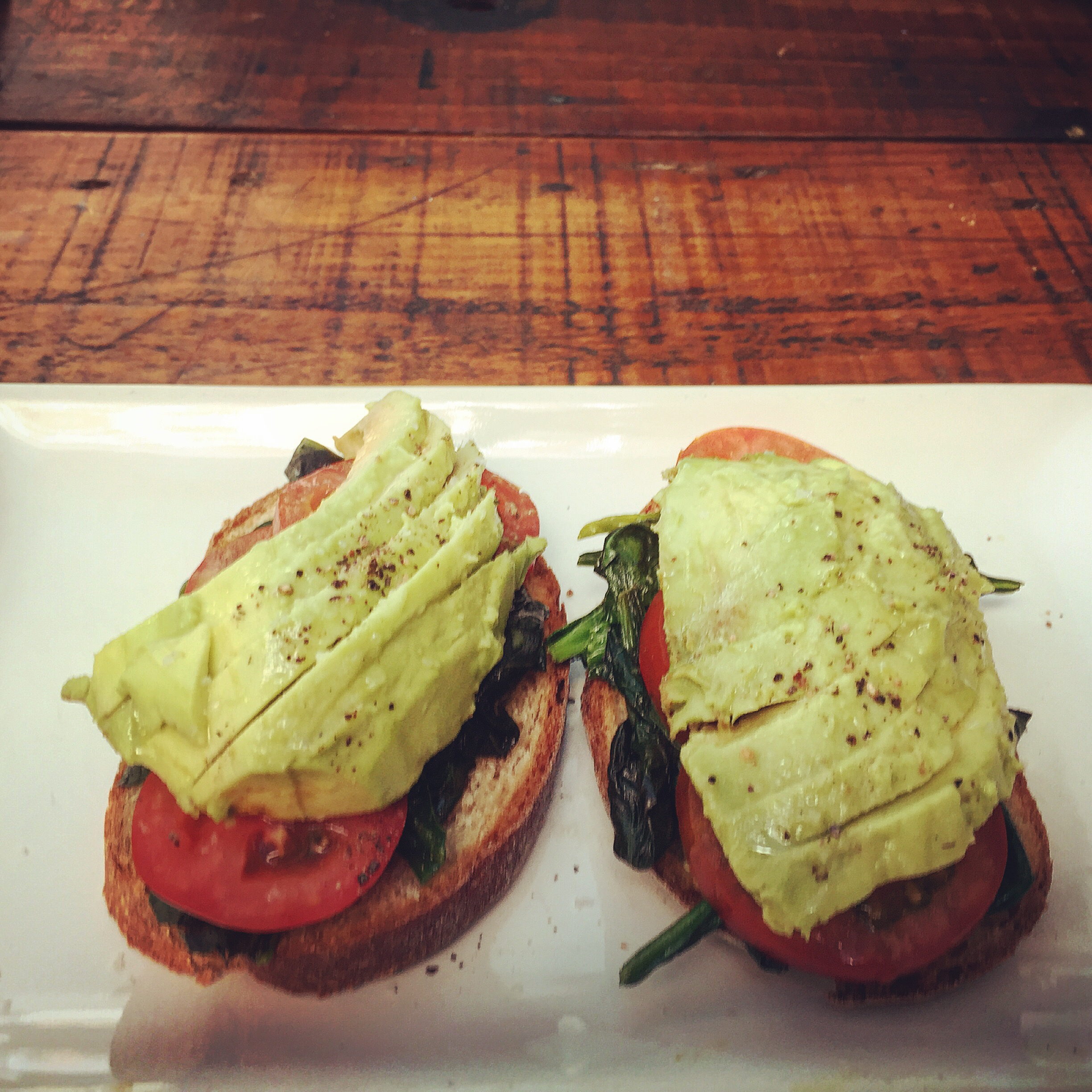 Avocado on Toast - Wheat bread, avocado, wilted spinach, fresh tomatoes and lime.