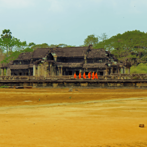A group of monks walking towards one of the temples of Angkor Wat.