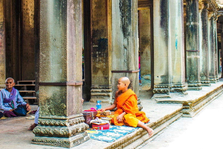 A young monk sits and chants and blesses the visitors of Angkor Wat for donations.