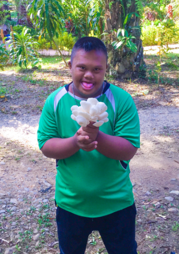 One of the students from the special school harvesting mushrooms.