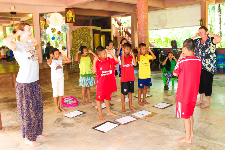 """Two of the guests al Eco-Logic volunteer with the kids during Saturday Creative School, teaching them """"Heads, Shoulders, Knees, and Toes""""."""