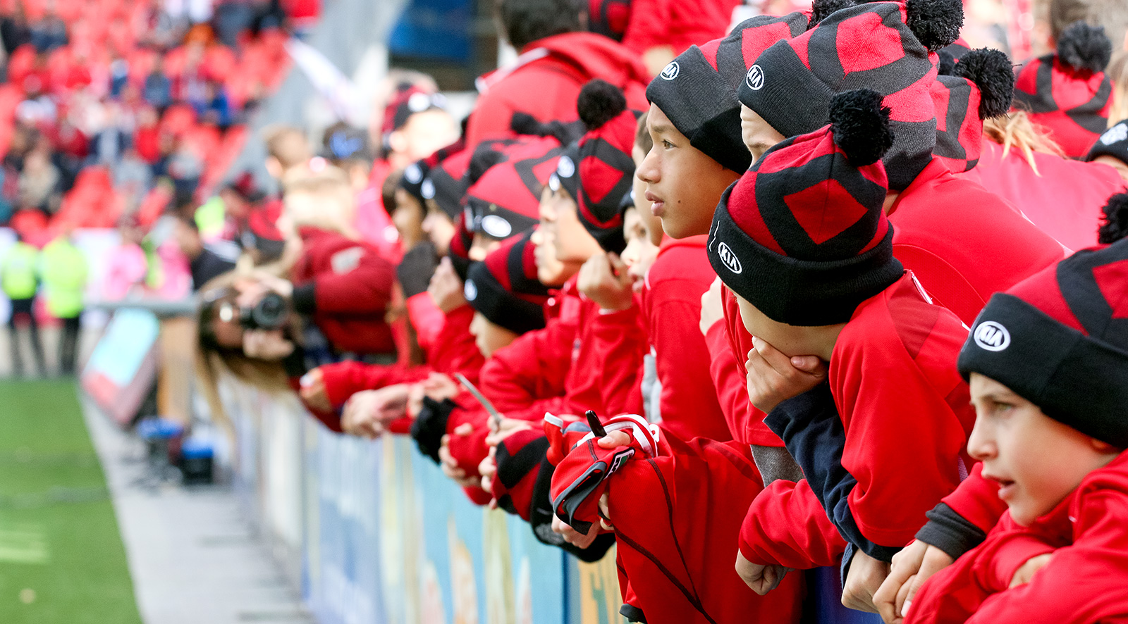 Young TFC fans watching the practice from the sidelines before the match begins.