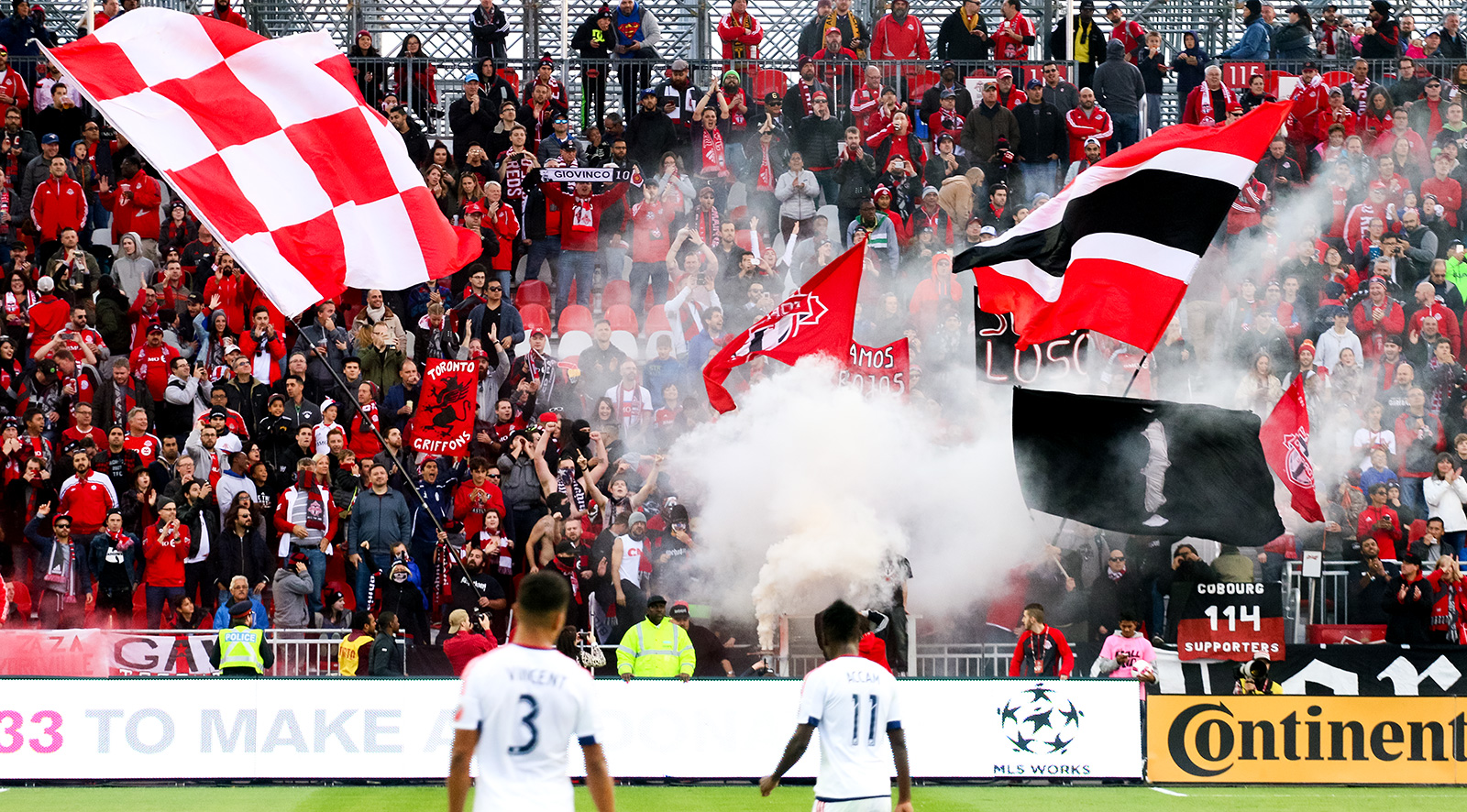 Toronto FC supporters doing their thing while two Chicago Fire players look on.