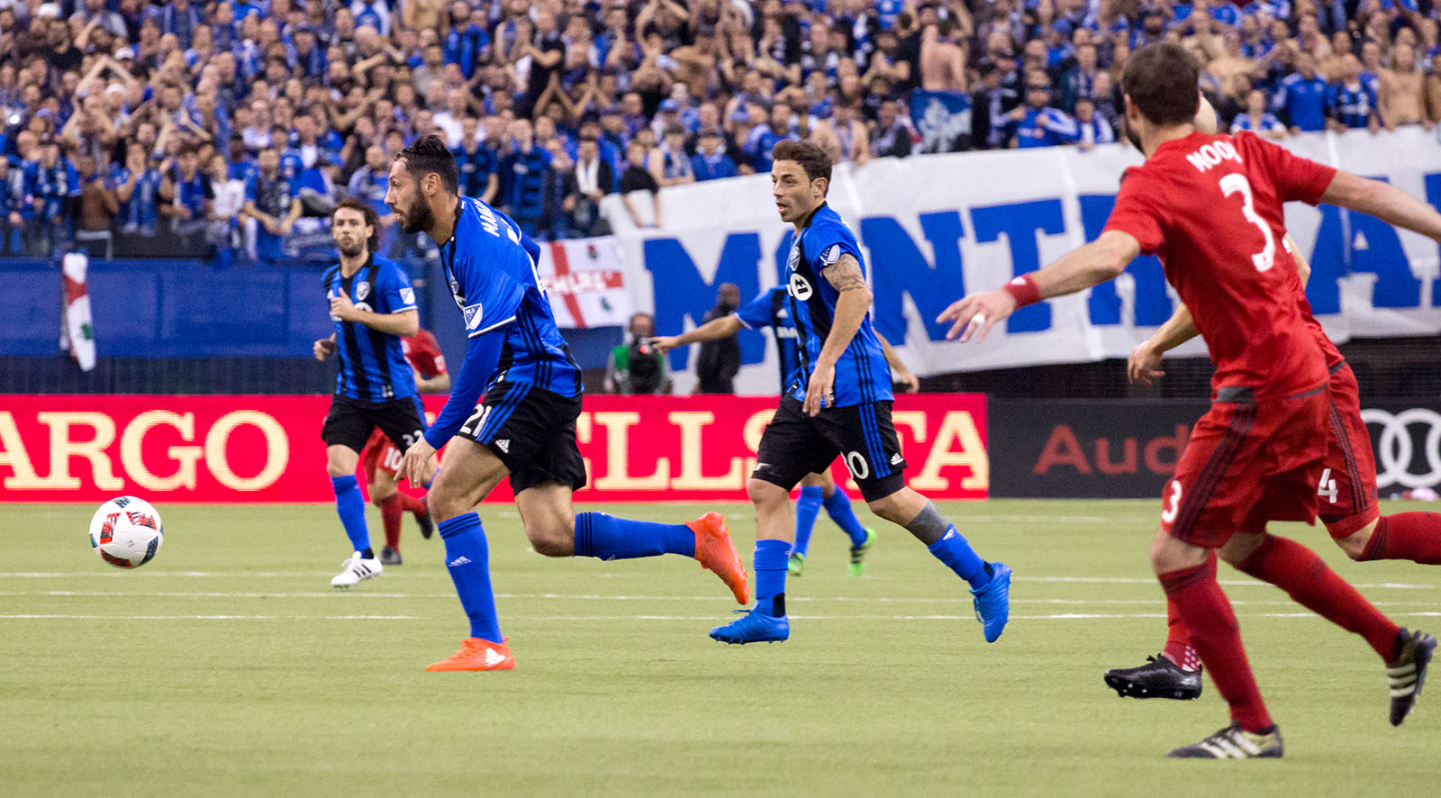 Montreal playing the ball away from Toronto FC during the MLS Cup Playoffs.