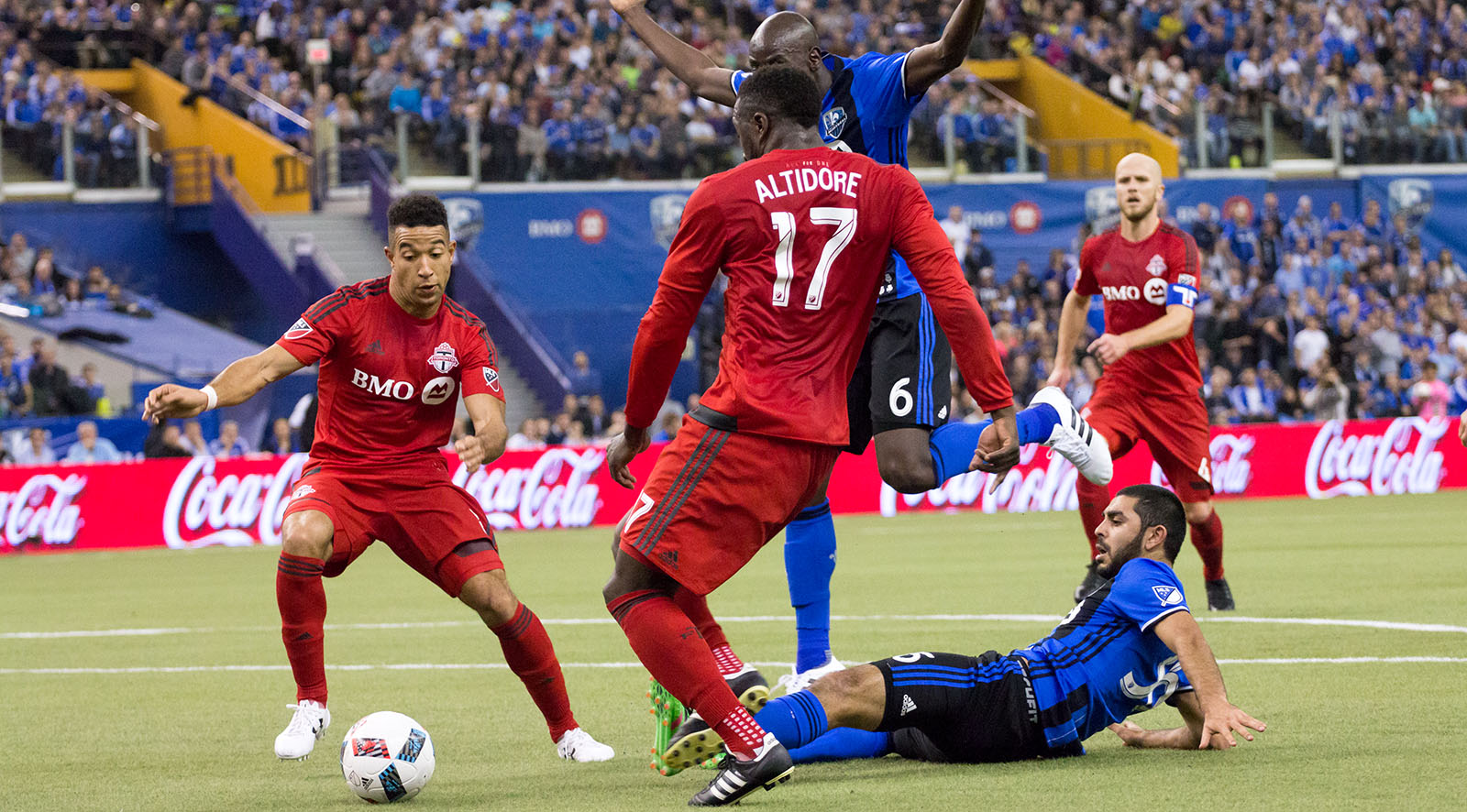 Montreal Impact and Toronto FC players scramble after the ball after a sliding tackle.