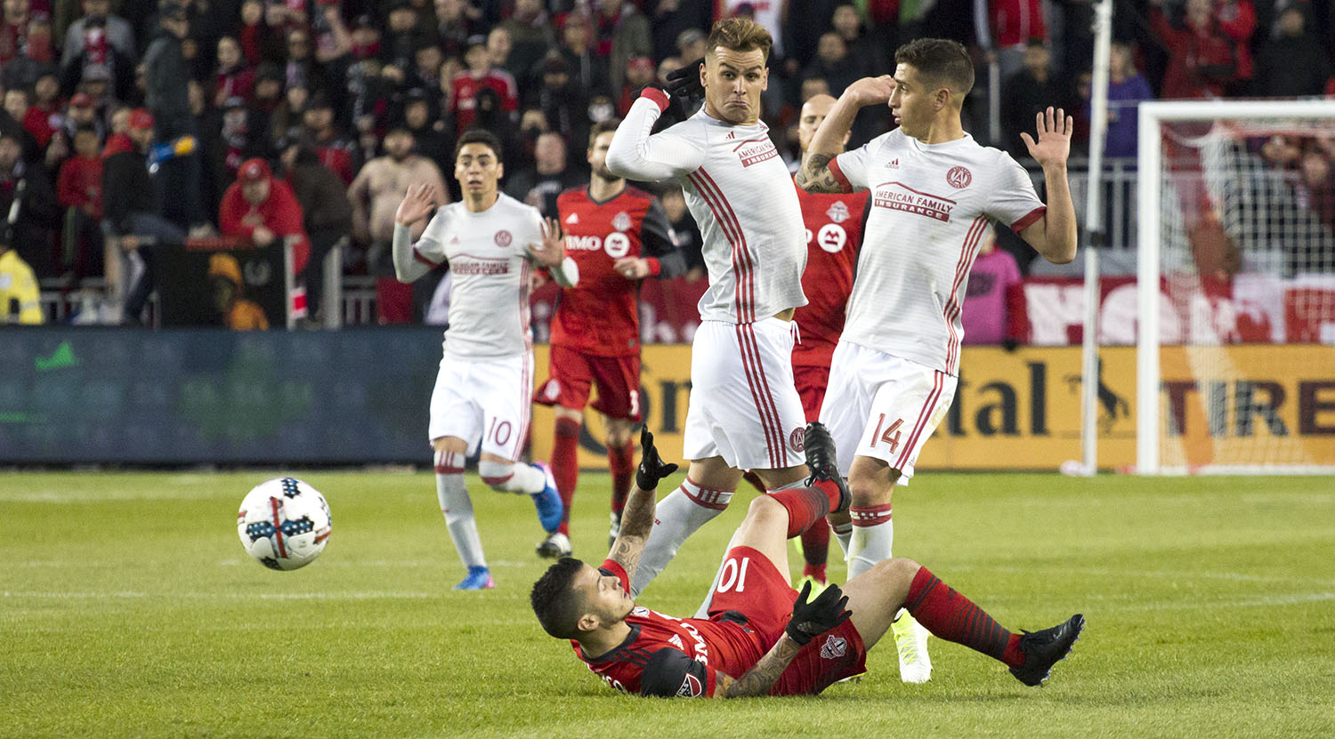 Sebastian Giovinco laying on the ground as two Atlanta United FC players act as if nothing had happened. Image by Dennis Marciniak.