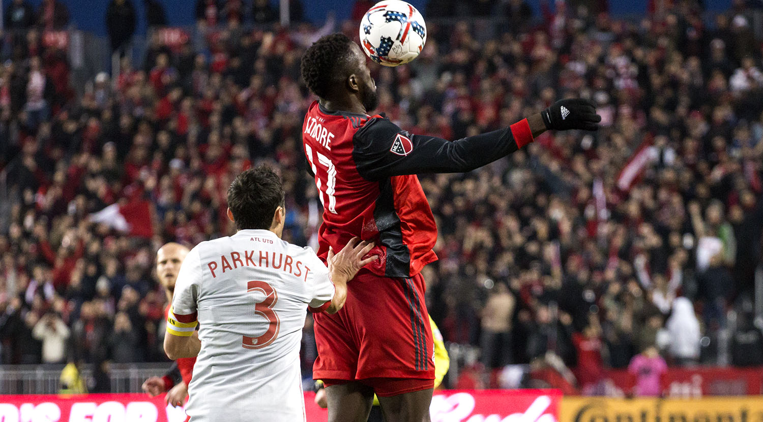 Jozy Altidore and Parkhurst go into the air for a header on the ball during a game at BMO Field. Image by Dennis Marciniak of denMAR Media.