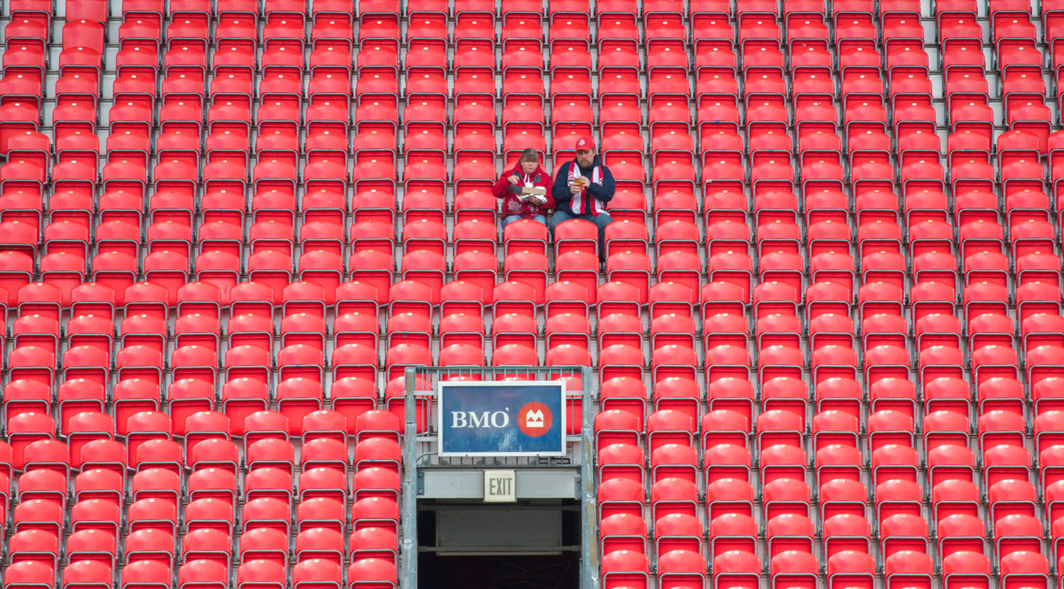 A couple enjoying some in stadium food before the Toronto FC v Minnesota United match on May 13, 2017 at BMO Field in Toronto, Canada. Image by Dennis Marciniak of denMAR Media.