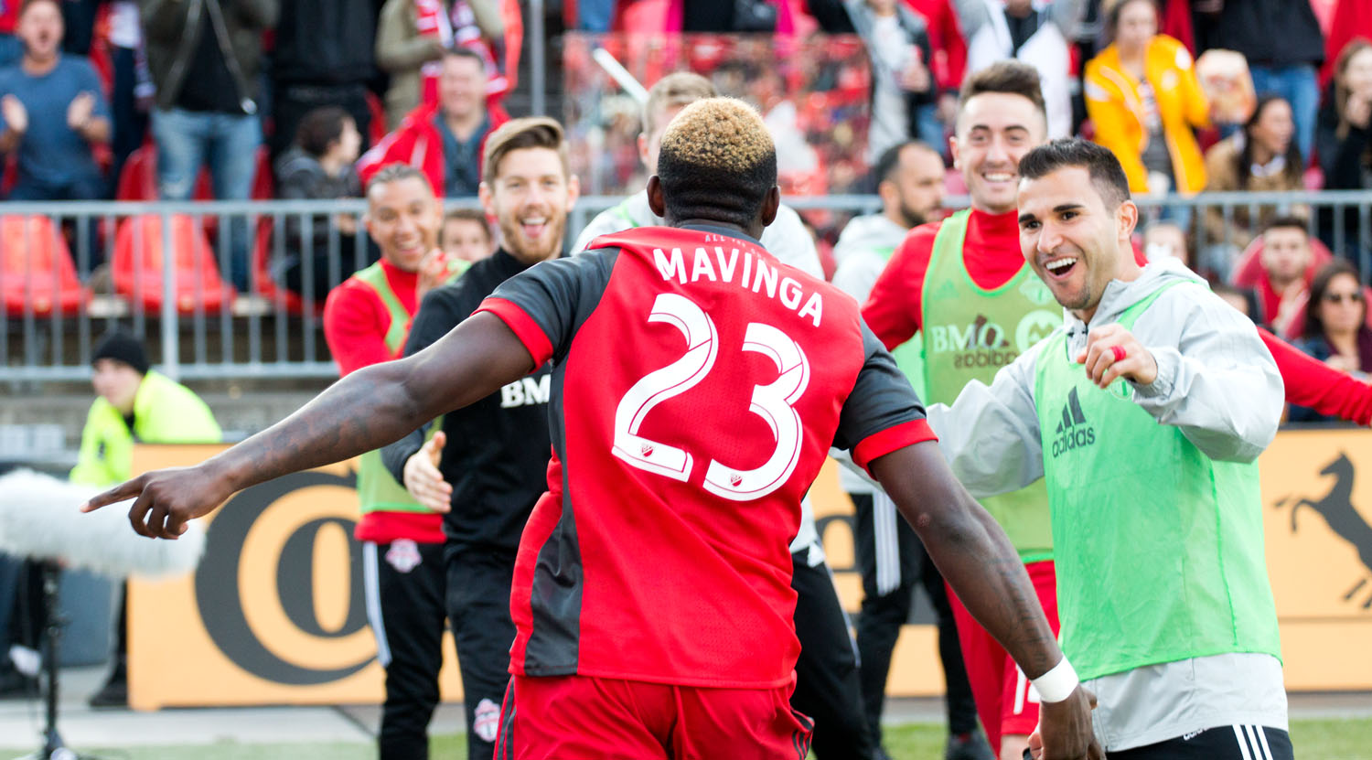 Chris Mavinga celebrating the second Toronto FC goal with players from the bench. Image by Dennis Marciniak of denMAR Photogrpahy.