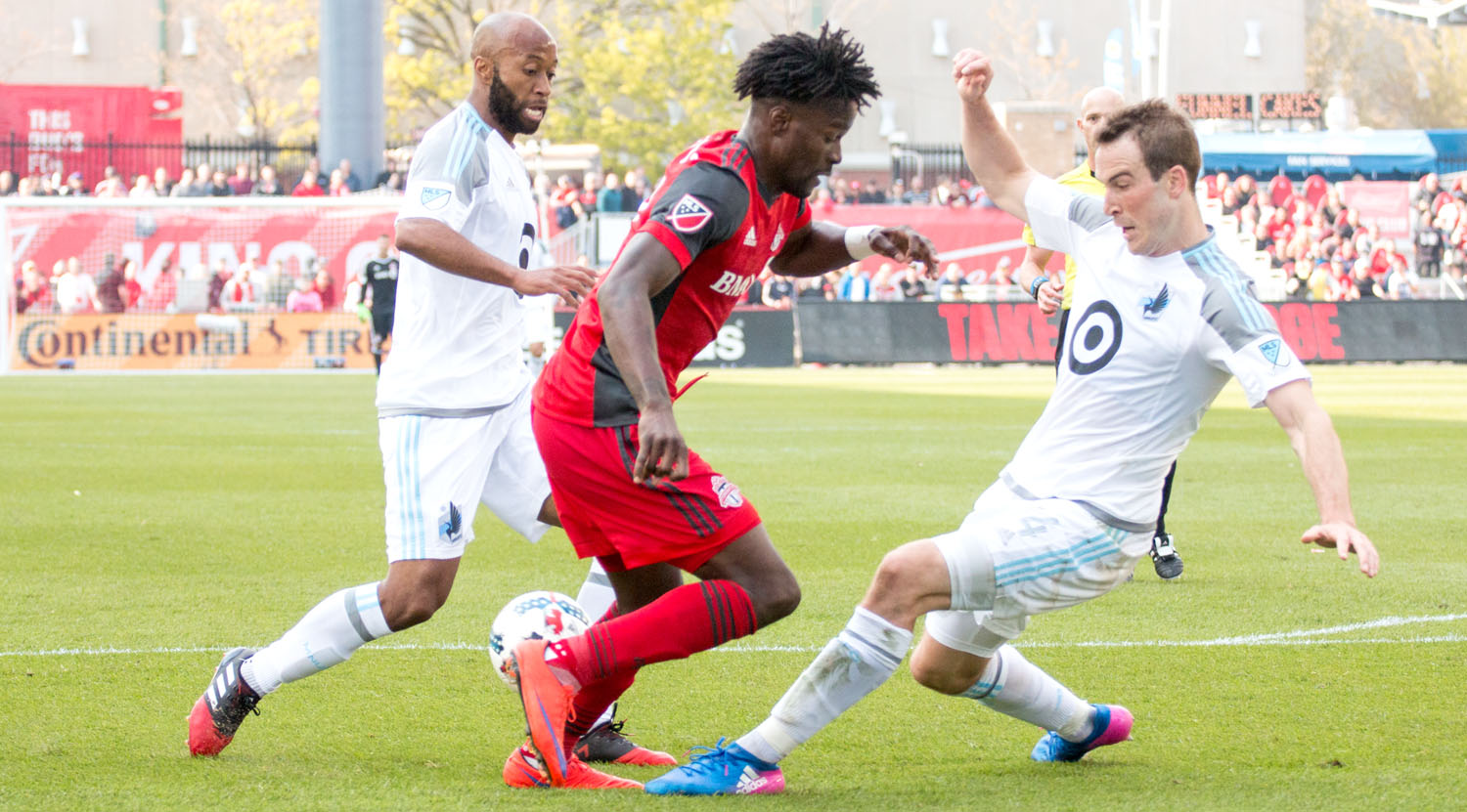 Tossaint Ricketts playing the ball around two Minnesota United FC players at BMO Field. Photo by Dennis Marciniak.
